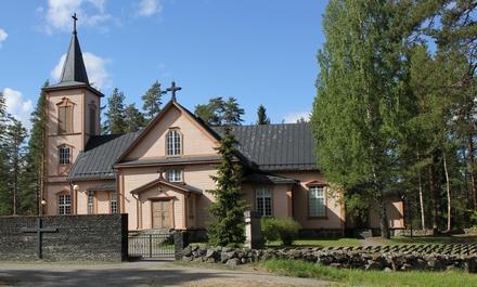 Vaaleanpunainen kirkkorakennus. Edessä kukkaistutuksia.
