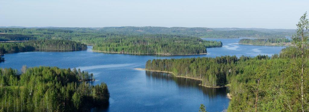 Näkymä Neitvuoren huipulta kohti sinistä järvimaisemaa, jossa metsäisiä saaria.